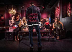 """L'affiche de la série """"Ladies Happy Hour"""". Elodie Cinquanta, Charlotte Deniel, Laurence Morisot, Marie-Eve Musy et Verena Lopes, assises au seond plan sur un canapé, regardent un homme qui leur fait face au premier plan."""
