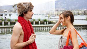 Tournage de la série Break Ups aux Bains des Pâquis avec Baptiste Gilliéron torse nu, une chapka sur la tête et Marie-Eve Musy en serviette de bain, un immense sac d'affaires de plage sur l'épaule.