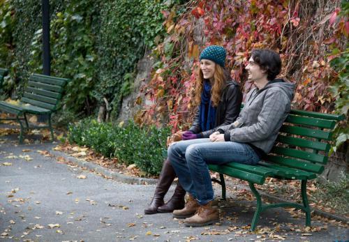 Sur le tournage du film Myrtille, un plan moyen de Marie-Eve Musy et Baptiste Gilliéron qui rient sur un banc dans un parc en automne.