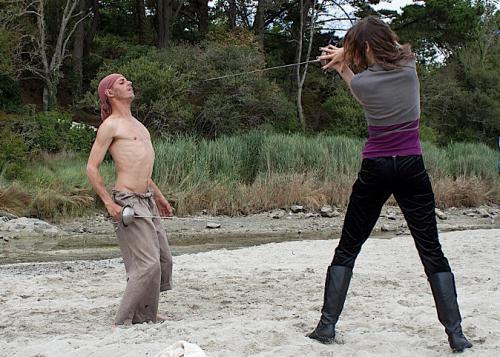 Marie-Eve Musy, en plein combat sur une plage durant le tournage d'Haraxome, tient Mehdi Rahim à sa merci avec son épée.